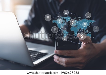 Currency exchange, money transfer, FinTech financial technology, Global business, online banking, interbank payment concept. Man using mobile phone and laptop computer with international currencies