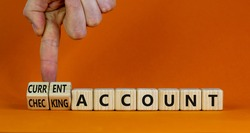 Current or checking account symbol. Businessman turns wooden cubes and changes words 'checking account' to 'current account'. Beautiful orange background, copy space. Business concept.