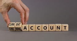 Current or checking account symbol. Businessman turns wooden cubes and changes words 'checking account' to 'current account'. Beautiful grey background, copy space. Business concept.