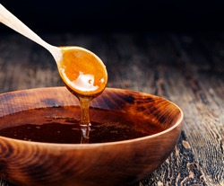 current thick and delicious sweet honey, a natural and healthy food product created by bees, natural bee honey has a viscous and thick consistency