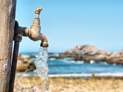 Current water flowing from tap against rocky beach. Shot in South Africa.