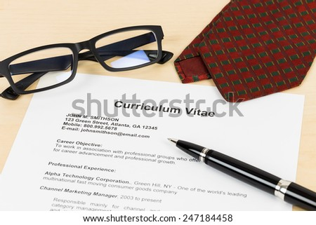 Curriculum vitae or CV with pen, glasses, and neck tie; concept job applying