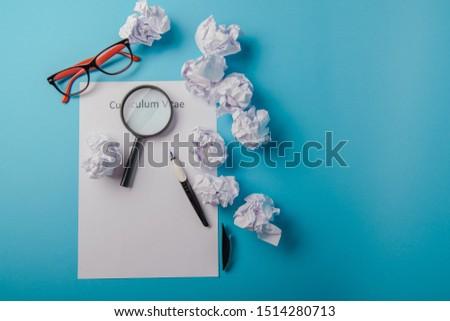 Curriculum vitae written on an blank white paper on blue background Stok fotoğraf ©