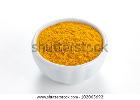 Curry ground (Madras Curry) in a white bowl on white background. Used as a spice in cuisines all over the world.