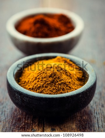 Curry powder and chili pepper in small containers - stock photo