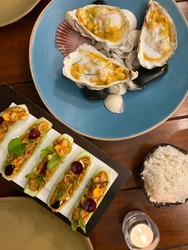 Curry sauce on oyster served in shell served with Thai appetizer made of shrimp salad served in cucumber bowl