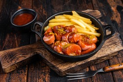 Currywurst Sausages with Curry spice on wursts served French fries in a pan. Dark wooden background. Top view