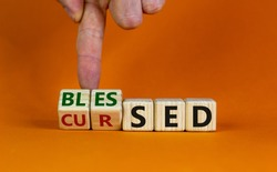 Cursed or blessed. Male hand flips a wooden cube and changes a word 'cursed' to 'blessed' or vice versa. Beautiful orange background, copy space. Religious and cursed or blessed concept.
