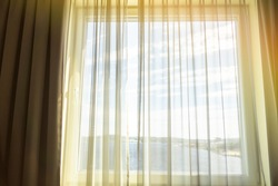 Curtain and window decoration interior of room.Defocused curtain window with sunlight in the early morning
