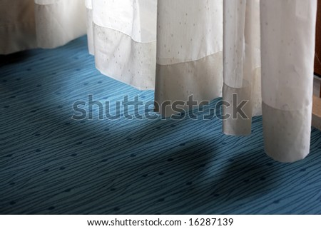 Curtain low hanging above a carpet covering