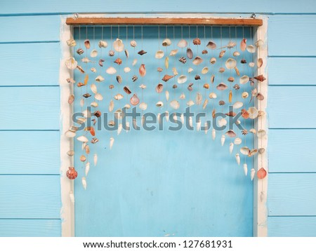 Curtain Shells Hanging On The Blue Door Stock Photo