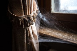 Curtain with spider web in an abandoned villa