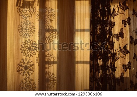 Curtains with contours of snowflakes and butterflies, backlit by the sun #1293006106