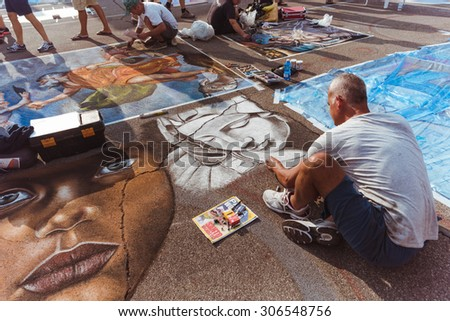 Curtatone, italy 15/08/2015: pavement street artist finishes painting over the asphalt in Madonnari word competition in italy of chalk paintings, from Santuario della Beata Vergine delle Grazie