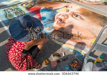 Curtatone, italy 15/08/2015: pavement street artist finishes painting over the asphalt in Madonnari word competition in italy of chalk paintings, from Santuario della Beata Vergine delle Grazie,