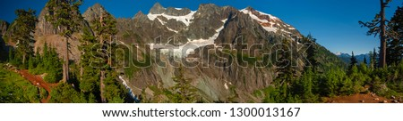 Curtis Glacier at the Foot of Imposing Mount Shuksan. Lower Curtis Glacier is in North Cascades National Park in the state of Washington. The glacier is on the western slopes of Mount Shuksan.