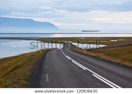 Curve Road through sea lagoon at twilight at North Iceland.