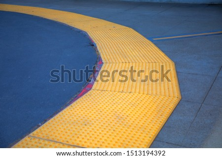 Curve Tactile paving with textured ground surface with markings, indicators for blind and visually impaired. Blindness aid, visual impairment, independent life concept.