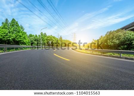 Curved asphalt highway and green forest #1104015563