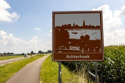Curved bike road next to freeway with traffic sign orienting entrance of the province area Achterhoek against a blue sky with clouds in countryroad with corn field on the side