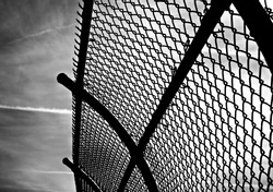 curved chain link fence against dramatic sky