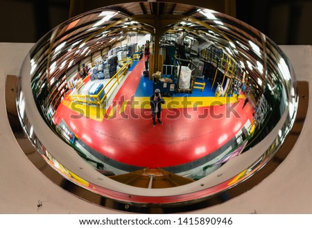 Curved circular mirror reflecting the inside of a factory for industry and production with bright reds, yellow, curved skylight reflection with photographer in the reflection worker health and safety #1415890946