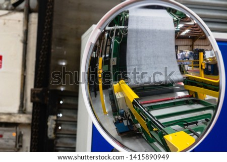 Curved circular mirror reflecting the inside of a factory for industry and production with bright reds, yellow, curved skylight reflection with photographer in the reflection worker health and safety #1415890949