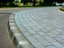 curved gray concrete sidewalk in low angle closeup view in diminishing perspective. interlocking brick pattern in running bond. formed concrete curb edge. abstract view. soft background of apartment
