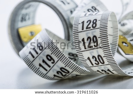 Curved measuring tape of the tailor close-up.