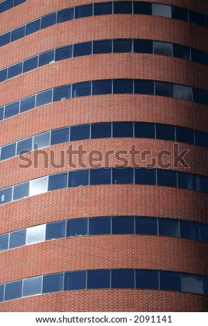 curved modern brick building with tinted windows background