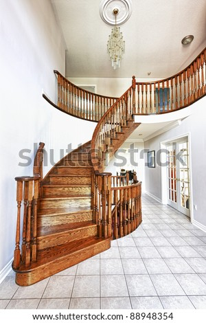 Curved oak staircase in luxury home entrance hall