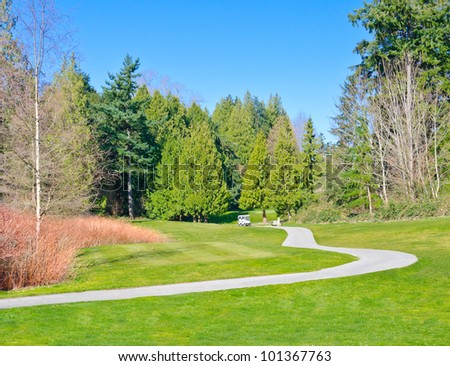 Curved path at a golf course with a golf cart on it.
