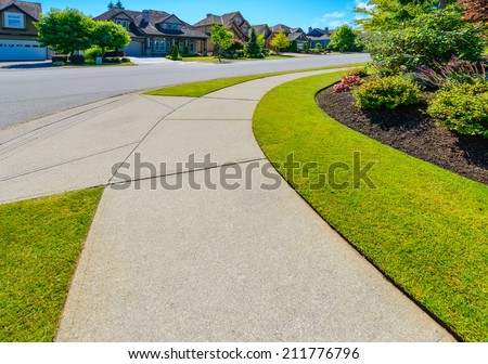 Curved pedestrian sidewalk in a nice neighborhood in the suburbs of Vancouver, Canada.