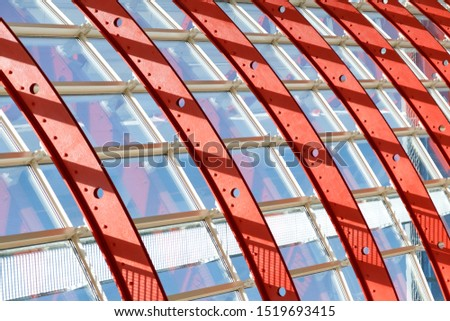 Curved red white metal structures hold the window systems. Through the glass passes bright sunlight. Illustration of the strength and airiness of the iron structure.