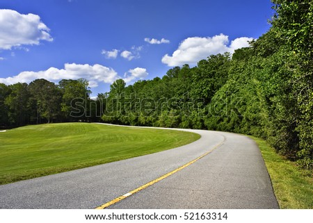Curved road by green tree line and blue sky above