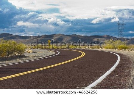 Curved road in the desert with dramatic sky
