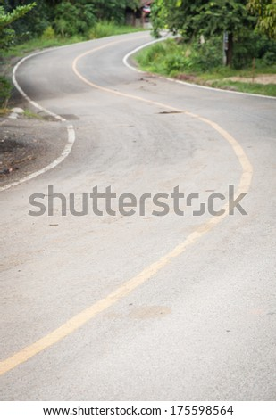Curved road is curved, not much. The side of the road with a tree.