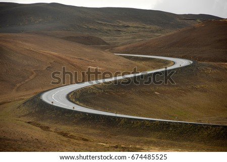 Curved Road leading through a hill in Iceland