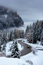 Curved road with dark car in the Italian Alps in South Tyrol, during winter / Evening with low clouds over the valley