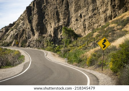 Curved road with Windy road ahead signpost