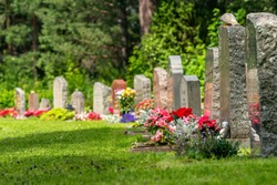 Curved row of tombstones with red and pink flowers on a beautiful and well cared cemetery in Sweden