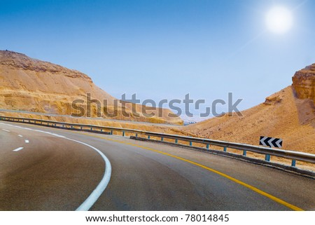 curved sandy road blue sky and sun on the way in Israel