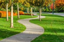 Curved sidewalk, path, trail at the empty street. Neighborhood scenery.