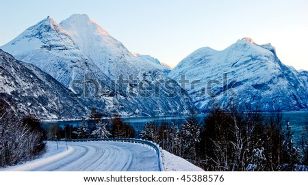 Stock Photo Curved snowy road in Norway, winter