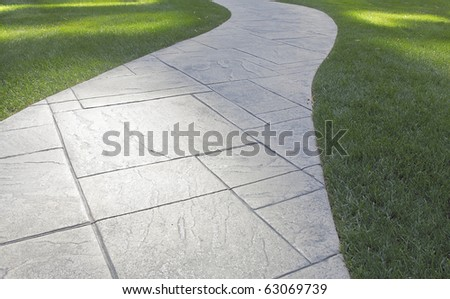 Curved stone pathway leading through lawn