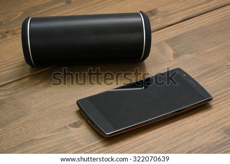 Curved touchscreen smartphone and Wireless portable bluetooth speaker on a wooden board