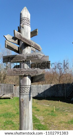 Curved wooden pointing on the crossroad in old rus style. Show way to choose directions to go. Pointer from wood on blue sky background #1102791383