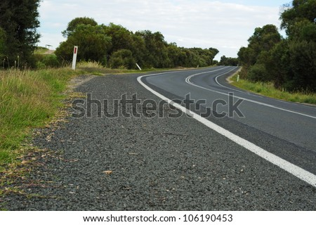 Curving black asphalt road with white marking lines from low point at roadside, trees, clouds on blue sky in background