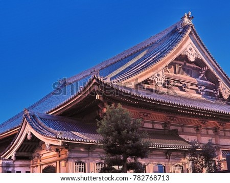 Curving Japanese temple roof lines. Shows the layered curves in the design, and color variations in the woods used. Flows from top right to left with open space top left on clear blue sky background #782768713
