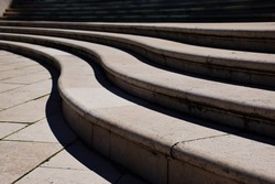 curving stone steps in exterior space. bright lights and shadows. background image. rectangular stone floor slab. S shape stair in abstract diminishing perspective.